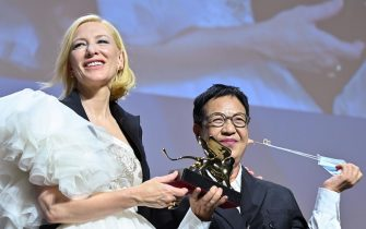 Hong-Kong director Ann Hui (R) takes off her face mask as she acknowledges receiving a Golden Lion award for Lifetime Achievement from Jury President of the 77th Venice Film festival, Australian-US actress Cate Blanchett, during a ceremony on the seventh day of the 77th Venice Film Festival, on September 8, 2020 at Venice Lido, during the COVID-19 infection, caused by the novel coronavirus. (Photo by Alberto PIZZOLI / AFP) (Photo by ALBERTO PIZZOLI/AFP via Getty Images)