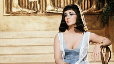 (Original Caption) 1962-Rome, Italy: Elizabeth Taylor as Cleopatra, is shown seated on a chair in front of a stairwell, on the set in Rome where the movie is being shot.