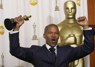 """HOLLYWOOD, United States:  Best Actor Jamie Foxx pumps his fists, hoisting his trophy, at the Kodak Theater in Hollywood, California, 27 February, 2005, during the 77th Academy Awards. Foxx won for his performance in """"Ray.""""  AFP PHOTO/ROBYN BECK  (Photo credit should read ROBYN BECK/AFP via Getty Images)"""