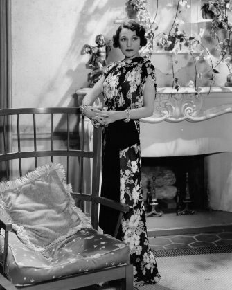 1937:  White flowers blossom on a black background on this attractive evening gown worn by Alice Brady (1892 - 1939) in her new film 'Mama Steps Out', directed by George B Seitz for MGM.  (Photo by Hulton Archive/Getty Images)