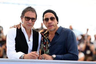 """French director Samuel Benchetrit (L) and French rapper and actor JoeyStarr pose during a photocall for the film """"Cette Musique ne joue pour Personne"""" (Love Songs For Tough Guys) at the 74th edition of the Cannes Film Festival in Cannes, southern France, on July 10, 2021. (Photo by Valery HACHE / AFP) (Photo by VALERY HACHE/AFP via Getty Images)"""