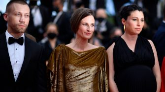 """French actress Camille Cottin (C) and director Rachel Lang (R) arrive for the screening of the film """"Mon Legionnaire"""" at the 74th edition of the Cannes Film Festival in Cannes, southern France, on July 15, 2021. (Photo by John MACDOUGALL / AFP) (Photo by JOHN MACDOUGALL/AFP via Getty Images)"""