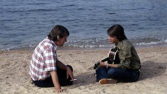 Il cantautore italiano Fabrizio De André con il figlio Cristiano seduti su una spiaggia mentre suonano e cantano insieme. Italia, Sardegna, 1978