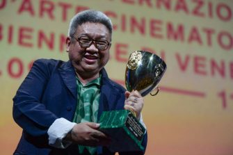 """Filipino director Erik Matti acknowledges receiving, on behalf of actor John Arcilla, the Coppa Volpi for Best Actor in """"On the Job: The Missing 8"""" during the closing ceremony of the 78th Venice Film Festival on September 11, 2021 at Venice Lido. (Photo by Filippo MONTEFORTE / AFP) (Photo by FILIPPO MONTEFORTE/AFP via Getty Images)"""