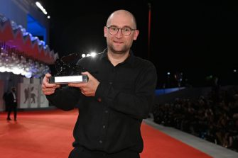 """VENICE, ITALY - SEPTEMBER 11:  Director Laurynas Bareisa poses with the Orizzonti Award for Best Film for """"Piligrimai"""" (Pilgrims) on the closing ceremony red carpet during the 78th Venice International Film Festival on September 11, 2021 in Venice, Italy. (Photo by Pascal Le Segretain/Getty Images)"""