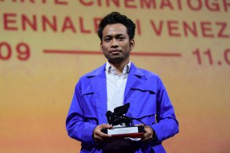 """Director Kavich Neang acknowledges receiving, on behalf of actor Piseth Chhun, the Orizzonti Award for Best Actor for """"White Building"""" during the closing ceremony of the 78th Venice Film Festival on September 11, 2021 at Venice Lido. (Photo by Filippo MONTEFORTE / AFP) (Photo by FILIPPO MONTEFORTE/AFP via Getty Images)"""