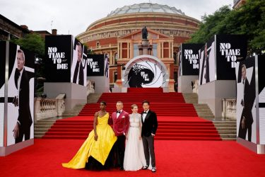 """English actor Lashana Lynch (L), English actor Daniel Craig (C) and French actor Lea Seydoux (2R) and US film director Cary Joji Fukunaga pose on the red carpet after arriving to attend the World Premiere of the James Bond 007 film """"No Time to Die"""" at the Royal Albert Hall in west London on September 28, 2021. - Celebrities and royals walk the red carpet in central London on Tuesday for the star-studded but much-delayed world premiere of the latest James Bond film, """"No Time To Die"""". (Photo by Tolga Akmen / AFP) (Photo by TOLGA AKMEN/AFP via Getty Images)"""