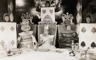 """(Original Caption) 1933- Picture shows a scene from the movie, """"Alice in Wonderland"""", written by Lewis Carroll. Alice(Charlotte Henry) is shown seated between the two chess pieces in a chair with """"Queen Alice"""" written on it. Undated photo circa 1930s-40s."""