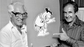 """The creators of """"The Flintstones,"""" the popular animated series, hold up a drawing of Fred Flintstone."""