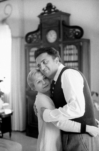 A tender hug between the famous Italian movie director Federico Fellini and Giulietta Masina, in the sunny living room of their house in Rome; Fellini thanks with humor her beloved wife and muse, who has just tied his tie; since their first meeting in 1942, the two are a couple not only in life, but also in art. Rome (Italy), the 50's. (Photo by Carlo Bavagnoli/Mondadori via Getty Images)