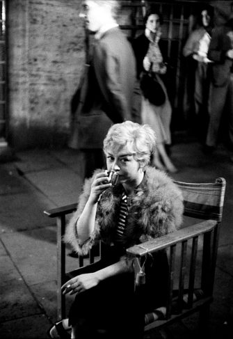 Giulietta Masina, seated outside with just a fur shrug over the scene dress, sips something to warm her up in the movie set of Nights of Cabiria; the Italian actress plays the starring role of Cabiria (nickname of Maria Ceccarelli), a young woman forced into prostitution after being robbed by her boyfriend. Rome (Italy), 1957. (Photo by Carlo Bavagnoli/Mondadori via Getty Images)