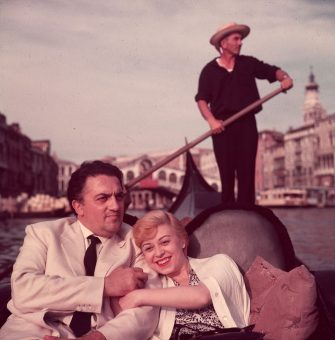 circa 1955:  Italian film director Federico Fellini (1920 - 1993) and his wife, actor Giulietta Masina (1920 - 1994), hold hands and smile while sitting in a gondola with a gondolier rowing in the background, Venice, Italy.  (Photo by Hulton Archive/Getty Images)