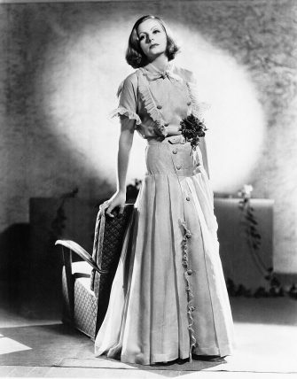 (Original Caption) The Feminine Mode. The tailored theme is combined with femininity in this ensemble of pale blue organdie, worn by Greta Garbo, MGM star. The double breasted blouse is held in with a tailored belt and skirt consisting of wide box pleats.