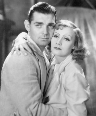 (Original Caption) Gable's Girls. It was a dreamy eyed young Clark Gable who clashed romantically with Greta Garbo in Susan Lennox, early in his film career. Today, Gable makes love to current movie Queens like Yvonne De Carlo, his leading lady in Warner Brother's Band of Angels.