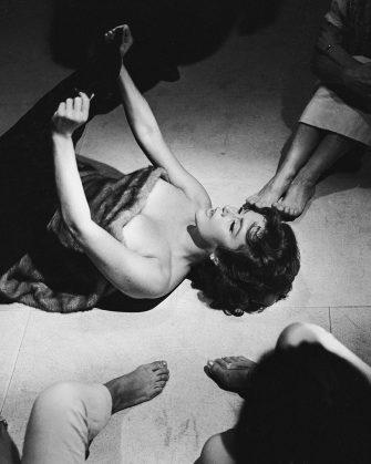 1960:  Nadia Gray (1923 - 1994) lies naked on the floor covered in furs in a party scene from 'La Dolce Vita', directed by Federico Fellini.  (Photo via John Kobal Foundation/Getty Images)