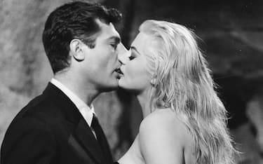 1960:  Marcello Mastroianni (1924 - 1996) and Anita Ekberg share a screen kiss in 'La Dolce Vita', directed by Federico Fellini.  (Photo via John Kobal Foundation/Getty Images)