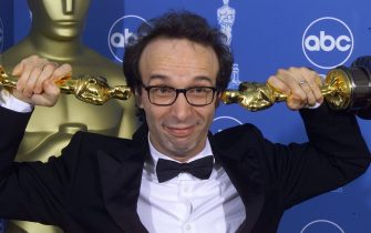 "LOS ANGELES, UNITED STATES:  Double Oscar winner for Best Foreign Film and Best Actor Roberto Benigni poses for photographers 21 March, 1999 at the Dorothy Chandler Pavilion in Los Angeles during the 71st Annual Academy Awards. Begnini was awarded in both categories for ""Life Is Beautiful"". (ELECTRONIC IMAGE)    AFP PHOTO  Hector MATA (Photo credit should read HECTOR MATA/AFP via Getty Images)"