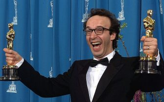 """LOS ANGELES, CA - MARCH 21:  Actor Roberto Benigni of Italy holds his two Oscars for Best Foreign Language Film and Best Actor for """"Life is Beautiful""""  at the 71st Annual Academy Awards in Los Angeles, CA 21 March 1999.  (Photo credit should read VINCE BUCCI/AFP via Getty Images)"""