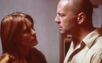 """381803 05:  Robin Wright Penn (left) stars as Audrey, David Dunn's (Bruce Willis, right) vulnerable wife who, with their marriage failing, finds new meaning in their relationship following a catastrophic train wreck in which David is the sole survivor, in Touchstone Pictures' riveting, suspense-filled action thriller, """"Unbreakable.""""  (Photo by Frank Masi, S.M.P.S.P./Touchstone Pictures/Newsmakers)"""