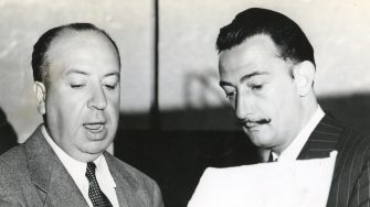 Film director Alfred Hitchcock (fore left) speaks with Spanish surrealist painter Salvador Dali (right), who designed sets and a devised a 'dream' sequence for Hitchcock's film 'Spellbound, , 1944. (Photo by PhotoQuest/Getty Images)