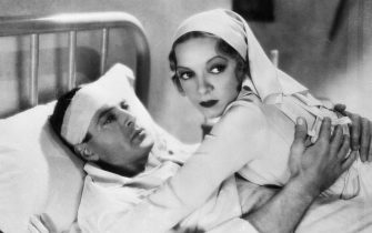 Actors Helen Hayes, as Catherine Barkley, and Gary Cooper, as Frederick Henry, embrace in a hospital bed in a scene from the 1932 version of A Farewell to Arms. | Based on: 'A Farewell to Arms' by Ernest Hemingway.