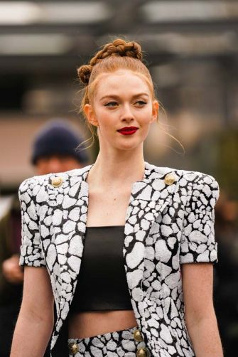 PARIS, FRANCE - FEBRUARY 28: Larsen Thompson wears a black cropped top, a black and white jacket with printed cow patterns and shoulder pads, pants with golden buttons, outside Balmain, during Paris Fashion Week - Womenswear Fall/Winter 2020/2021, on February 28, 2020 in Paris, France. (Photo by Edward Berthelot/Getty Images)