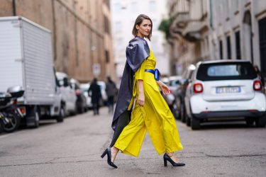MILAN, ITALY - FEBRUARY 20: Landiana Cerciu wears a yellow dress, a blue belt bag, a black leather cape, outside Max Mara, during Milan Fashion Week Fall/Winter 2020-2021 on February 20, 2020 in Milan, Italy. (Photo by Edward Berthelot/Getty Images)