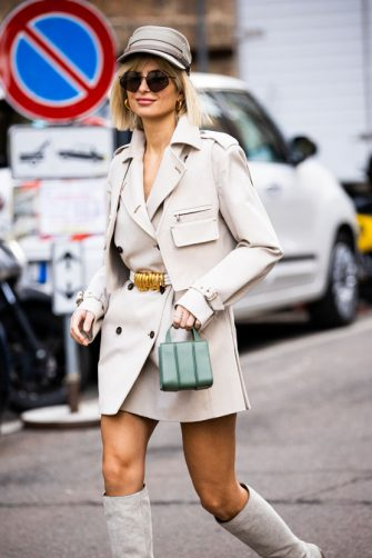 MILAN, ITALY - FEBRUARY 20: Xenia Adonts, wearing a light beige trench coat, taupe hat, light beige boots and green bag, is seen outside Max Mara show, during Milan Fashion Week Fall/Winter 2020-2021 on February 20, 2020 in Milan, Italy. (Photo by Claudio Lavenia/Getty Images)