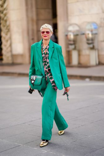 MILAN, ITALY - FEBRUARY 20: Elisa Nalin wears red sunglasses, a green oversized blazer jacket, a green and pink shirt, a green leather bag, flared pants, golden pointy shoes, outside Vivetta, during Milan Fashion Week Fall/Winter 2020-2021 on February 20, 2020 in Milan, Italy. (Photo by Edward Berthelot/Getty Images)