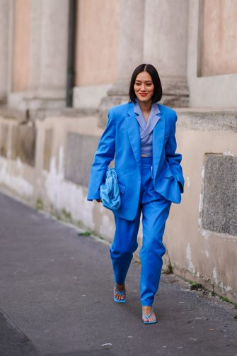 MILAN, ITALY - FEBRUARY 20: Tiffany Hsu wears a blue oversized blazer jacket, a blue leather The Pouch Bottega Veneta bag, blue pants, sandals, outside Koche x Pucci, during Milan Fashion Week Fall/Winter 2020-2021 on February 20, 2020 in Milan, Italy. (Photo by Edward Berthelot/Getty Images)