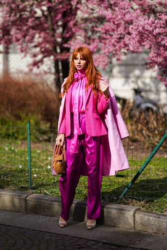 MILAN, ITALY - FEBRUARY 20: A guest wears a pink coat, a neon pink silky shiny lustrous shirt, a jacket, silky pants, a brown leather bag, pointy shoes, outside Koche x Pucci, during Milan Fashion Week Fall/Winter 2020-2021 on February 20, 2020 in Milan, Italy. (Photo by Edward Berthelot/Getty Images)
