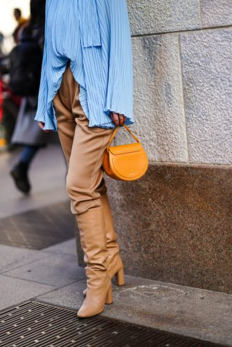 MILAN, ITALY - FEBRUARY 20: A guest wears a blue pleated ruffled top with flare sleeves, brown pants, brown leather pointy boots, a brown leather bag, outside Vivetta, during Milan Fashion Week Fall/Winter 2020-2021 on February 20, 2020 in Milan, Italy. (Photo by Edward Berthelot/Getty Images)