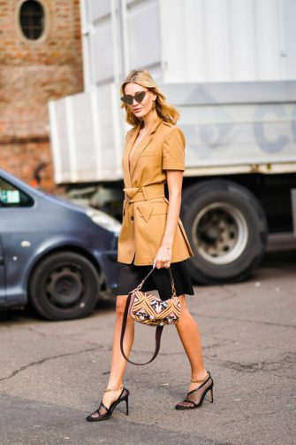 MILAN, ITALY - FEBRUARY 20: A guest wears sunglasses, a brown jacket, a belt, a black skirt, mesh pointy shoes, a Fendi bag, outside Max Mara, during Milan Fashion Week Fall/Winter 2020-2021 on February 20, 2020 in Milan, Italy. (Photo by Edward Berthelot/Getty Images)