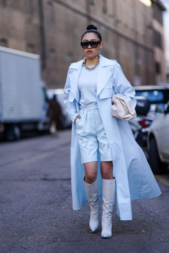 """MILAN, ITALY - FEBRUARY 20: Jaime Xie wears sunglasses, a blue trench coat, a white leather """"The Pouch"""" bag from Bottega Veneta, shorts, white boots, outside Max Mara, during Milan Fashion Week Fall/Winter 2020-2021 on February 20, 2020 in Milan, Italy. (Photo by Edward Berthelot/Getty Images)"""