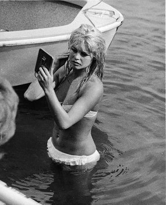 French actor Brigitte Bardot looks at her reflection in a mirror, while standing in the waters of Lake Leman, June 13, 1961. (Photo by Express Newspapers/Getty Images)