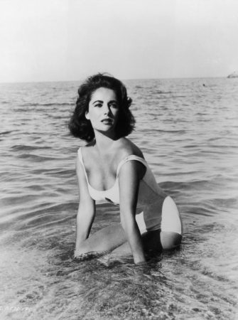 1959:  British born actor Elizabeth Taylor wears a white swimsuit while kneeling in the surf in a still from director Joseph L Mankiewicz's film 'Suddenly Last Summer'.  (Photo by Hulton Archive/Getty Images)