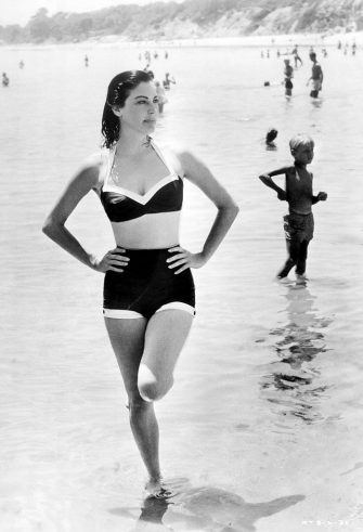 Actress Ava Gardner on the beach.  She wears a two-piece bathing suit and stands with one foot up in ankle-deep water.  Undated photograph.