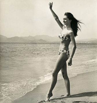 Brigitte Bardot, playing the role of Javotte Lemoine, waves from the shore in a scene from the 1952 French comedy Le Trou Normand.