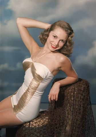 American actress Janet Leigh (1927 - 2004) sits and poses on a fake pier in a white and gold bathing suit, late 1940s. (Photo by Hulton Archive/Getty Images)
