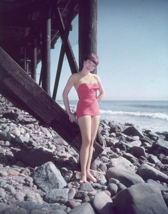 circa 1955:  Full-length portrait of American actor Shirley MacLaine, wearing a pink strapless swimsuit, standing on the rocks beneath a wooden pier by the seashore.  (Photo by Hulton Archive/Getty Images)