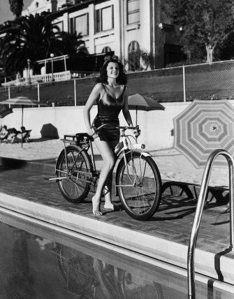 circa 1940:  American actor Rita Hayworth (1918 - 1987) poses on a bicycle in a swimsuit by the side of a swimming pool at the Beverly Hills Hotel, California.  (Photo by Hulton Archive/Getty Images)