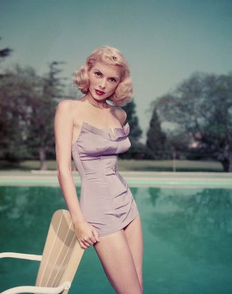 Portrait of American actress Janet Leigh (1927 - 2004) as she leans against a patio chair and wears a purple bathing suit next to a large swimming pool, 1950s. (Photo by Pictorial Parade/Getty Images)