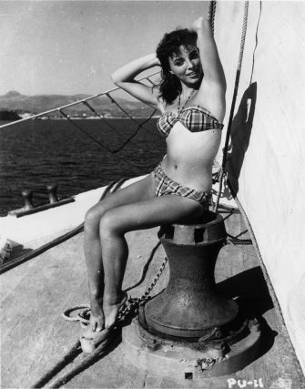 1955:  Film actress Joan Collins enjoying a sail in the sunshine of the Pacific. She is in Hollywood to play Bess Throckmorton, one of Elizabeth I's maids of honour in 'The Virgin Queen'.  (Photo by Hulton Archive/Getty Images)