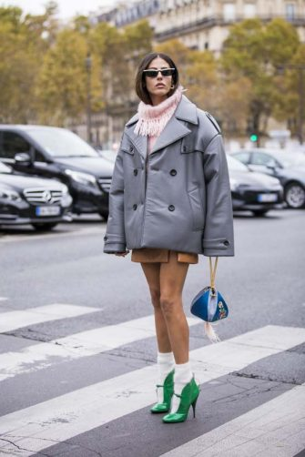 PARIS, FRANCE - OCTOBER 02: Gilda Ambrosio, wearing a pink sweater, beige mini skirt, green heels with white socks, blue bag and grey jacket, is seen before the Miu Miu show on October 2, 2018 in Paris, France. (Photo by Claudio Lavenia/Getty Images)