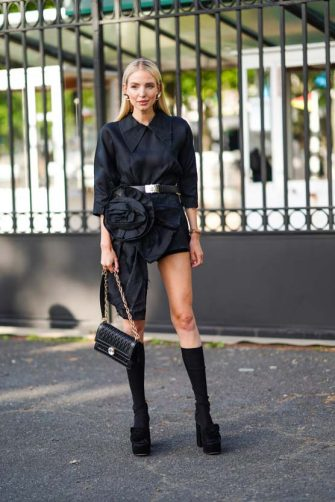 PARIS, FRANCE - JUNE 29: Leonie Hanne wears earrings, a black dress with an attached large flower, a belt, a black leather Miu Miu bag, long socks, black shoes, outside Miu Miu Club 2020,  on June 29, 2019 in Paris, France. (Photo by Edward Berthelot/Getty Images)