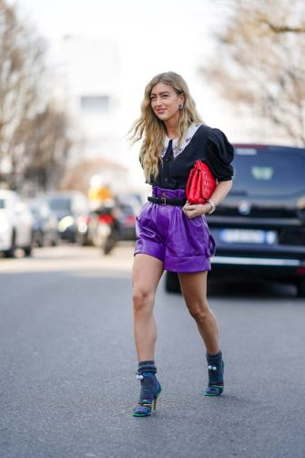 MILAN, ITALY - FEBRUARY 22: Emili Sindlev wears a ruffled black shirt with puff shoulder pads, a red quilted bag, purple leather shorts, gray wool socks, multicolor shoes, outside MSGM, during Milan Fashion Week Fall/Winter 2020-2021 on February 22, 2020 in Milan, Italy. (Photo by Edward Berthelot/Getty Images)
