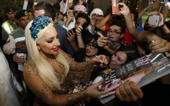 US pop star Lady Gaga signs her autograph for fans as she arrives at Dubai International airport on September 8, 2014, on her fourth world tour ArtRave: The Artpop Ball Tour, where she will perform at the at Meydan Racecourse on September 10. AFP PHOTO/ KARIM SAHIB        (Photo credit should read KARIM SAHIB/AFP via Getty Images)