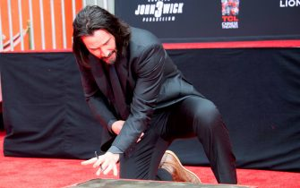 Actor Keanu Reeves signs his name in cement during his handprint ceremony at the TCL Chinese Theatre IMAX forecourt on May 14, 2019 in Hollywood, California. (Photo by VALERIE MACON / AFP)        (Photo credit should read VALERIE MACON/AFP via Getty Images)