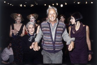 The fashion designer Ottavio Missoni at the end of a fashion show, while walking on the catwalk, holding by hands his wife Rosita Missoni (Rosita Jelmini) and a model. Behind other models. Italy, 1984. (Photo by Angelo Deligio/Mondadori via Getty Images)