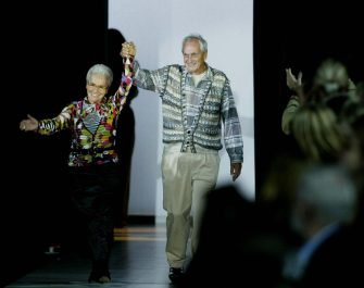 Italian Tai (R) and Rosita Missoni acknowledge applause on the catwalk at the end of the Missoni collection during the last day of the Milan 2004 Spring/Summer fashion week 05 October 2003. The show is a milestone in every sense as it marks 50 years since the company was founded by Tai and Rosita and 50 years since they married.     AFP PHOTO/PAOLO COCCO  (Photo credit should read PAOLO COCCO/AFP via Getty Images)